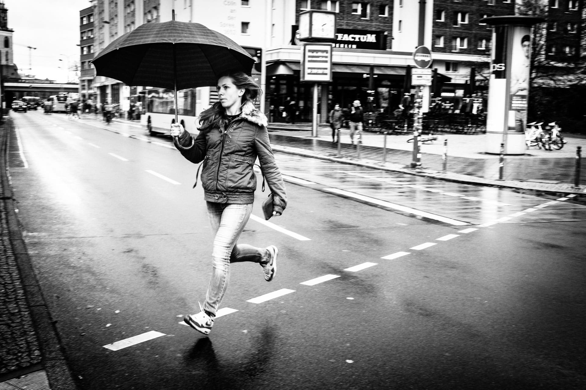 Running girl with her umbrella on a dotted line